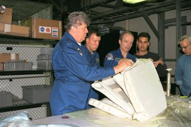 STS-91 Mission Specialist Valery Ryumin with the Russian Space Agency, Pilot Dominic Gorie, Commander Charles Precourt, and Adam Flagan, a crew equipment trainer from Johnson Space Center, inspect a flight pack as part of Crew Equipment Interface Test, or CEIT, activities in KSC's Orbiter Processing Facility Bay 2. During CEIT, the crew have an opportunity to get a hands-on look at the payloads with which they'll be working on-orbit. The STS-91 crew are scheduled to launch aboard the Shuttle Discovery for the ninth and final docking with the Russian Space Station Mir from KSC's Launch Pad 39A on May 28 at 8:05 EDT