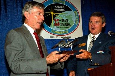 Astronaut John Young (left), the keynote speaker at the Thirty-Fifth Space Congress, is presented with a model of the International Space Station by the Congress' General Chairman Bruce Melnick. Young is the associate director responsible for technical, operational and safety oversight of all NASA programs and activities assigned to the Johnson Space Center. Melnick, a former astronaut, is currently vice president of The Boeing Company and is responsible for the Payload Ground Operations Contract at Kennedy Space Center. The Thirty-Fifth Space Congress, sponsored by the Canaveral Council of Technical Societies, is being held in Cocoa Beach, Florida, from April 28 to May 1 and is a gathering of the world's aerospace community to discuss the status and future of space activities around the world