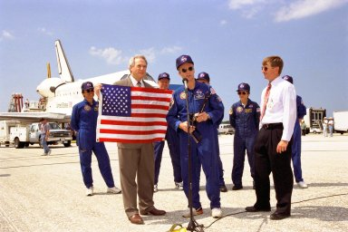 STS-91 Mission Commander Charles J. Precourt (at microphone) presents an American flag, a special wrench, and an optical disc to NASA Administrator Dan Goldin following Discovery's landing at KSC's Shuttle Landing Facility, as Phase I Shuttle/Mir Program Manager Frank Culbertson and the other members of the STS-91 flight crew look on. This landing not only concluded the STS-91 mission, but Phase I of the joint U.S.-Russian International Space Station Program as well. The flag rode aboard Mir from the beginning of the Phase I program, the wrench was used on Mir and will be used on the International Space Station, and the optical disc holds data recorded on Mir. All of these items were brought back to Earth from Mir by the STS-91 crew. Discovery's main gear touchdown on Runway 15 was at 2:00:18 p.m. EDT on June 12, 1998, on orbit 155 of the mission. The wheels stopped at 2:01:22 p.m. EDT, for a total mission-elapsed time of 9 days, 19 hours, 55 minutes and 1 second. The 91st Shuttle mission was the 44th KSC landing in the history of the Space Shuttle program and the 15th consecutive landing at KSC. Besides Commander Precourt, the STS-91 flight crew also included Pilot Dominic L. Gorie and Mission Specialists Wendy B. Lawrence, Franklin R. Chang-Diaz, Janet Lynn Kavandi and Valery Victorovitch Ryumin of the Russian Space Agency. Astronaut Andrew S. W. Thomas also returned to Earth from Mir as an STS-91 crew member after 141 days in space