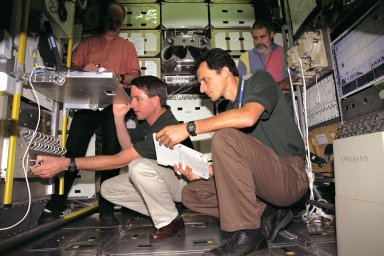 KENNEDY SPACE CENTER, FLA. -- While workers look on, STS-95 Mission Specialists Stephen K. Robinson, kneeling at left, and Pedro Duque inspect equipment inside the SPACEHAB module trainer at the SPACEHAB Payload Processing Facility in Cape Canaveral. STS-95 will feature a variety of research payloads, including the Spartan solar-observing deployable spacecraft, the Hubble Space Telescope Orbital Systems Platform, the International Extreme Ultraviolet Hitchhiker, and experiments on space flight and the aging process. STS-95 is targeted for an Oct. 29 launch aboard the Space Shuttle Discovery