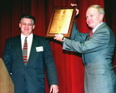 Center Director Roy Bridges (right) displays the 2000th ISO Certificate Plaque he was given by Dalton Lyon (left) of Det Norske Veritas (DNV), Inc., an international ISO certification organization, at a ceremony at KSC. The plaque is a representation of the ISO 9001 certification awarded to KSC by DNV. ISO 9001 comprises the most detailed, comprehensive set of standard requirements for quality programs established by the International Standards Organization. The presentation followed a successful independent audit by DNV of the KSC Management System in May of this year. The third-party auditors examined about 20 elements of KSC's system, including management responsibility, design control, documentation, test and inspection, and corrective action procedures. DNV found that KSC met or exceeded the stringent quality standards in all areas. KSC will use this certification as a tool to improve an already worldclass team. All NASA centers are required by NASA Administrator Daniel S. Goldin to be ISO 9001 registered by September 1999. NASA is the first federal agency to seek the quality certification