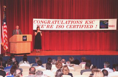 Center Director Roy Bridges speaks to KSC employees at the ISO certification ceremony held at the Training Auditorium. Bridges was presented an ISO 9001 certificate and plaque awarded to KSC by Det Norske Veritas (DNV), Inc., an international ISO certification organization. ISO 9001 comprises the most detailed, comprehensive set of standard requirements for quality programs established by the International Standards Organization. The presentation followed a successful independent audit by DNV of the KSC Management System in May of this year. The third-party auditors examined about 20 elements of KSC's system, including management responsibility, design control, documentation, test and inspection, and corrective action procedures. DNV found that KSC met or exceeded the stringent quality standards in all areas. KSC will use this certification as a tool to improve an already worldclass team. All NASA centers are required by NASA Administrator Daniel S. Goldin to be ISO 9001 registered by September 1999. NASA is the first federal agency to seek the quality certification. Next to Bridges is Heidi Hollingsworth, with the Center for Independent Living, who uses American Sign Language for any hearing-impaired employees in the audience
