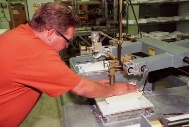 """In the Tile Fabrication Shop, Tony Rollins, with United Space Alliance, cuts a High-Temperature Reusable Surface Insulation (HRSI) tile on a gun stock contour milling machine. About 70 percent of a Space Shuttle orbiter?s external surface is shielded from heat by a network of more than 24,000 tiles formed from a silica fiber compound. HRSI tiles cover the lower surface of the orbiter, areas around the forward windows, upper body flap, the base heat shield, the """"eyeballs"""" on the front of the Orbital Maneuvering System (OMS) pods, and the leading and trailing edges of the vertical stabilizer and the rudder speed brake. They are generally 6 inches square, but may also be as large as 12 inches square in some areas, and 1 to 5 inches thick. More advanced materials such as Flexible Insulation Blankets have replaced tiles on some upper surfaces of the orbiter"""