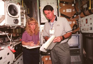 KENNEDY SPACE CENTER, FLA. -- Terri Schneider, a Timeline technician with United Space Alliance, and STS-95 Mission Specialist Stephen Robinson, Ph.D., look at documentation during SPACEHAB familiarization at the SPACEHAB Payload Processing Facility, Cape Canaveral. The mission, scheduled to launch Oct. 29, includes research payloads such as the Spartan solar-observing deployable spacecraft, the Hubble Space Telescope Orbital Systems Test Platform, the International Extreme Ultraviolet Hitchhiker, as well as the SPACEHAB single module with experiments on space flight and the aging process