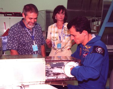 KENNEDY SPACE CENTER, FLA. -- Boeing SPACEHAB representatives Rick Rodriguez and Amy Haas watch STS-95 Mission Specialist Pedro Duque of Spain, representing the European Space Agency (ESA), maneuver inside a glove box which will be part of the mission, scheduled to launch Oct. 29. The STS-95 crew are participating in SPACEHAB familiarization at the SPACEHAB Payload Processing Facility. The mission includes research payloads such as the Spartan solar-observing deployable spacecraft, the Hubble Space Telescope Orbital Systems Test Platform, the International Extreme Ultraviolet Hitchhiker, as well as the SPACEHAB single module with experiments on space flight and the aging process