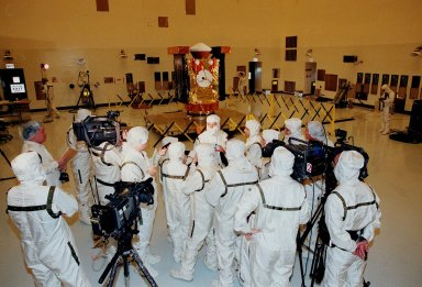 In the Payload Hazardous Servicing Facility, media representatives, dressed in protective suits, are updated by Project Manager Richard Grammier (center, top), with the Jet Propulsion Laboratory, about the Stardust spacecraft (in the background). Stardust is targeted for launch on Feb. 6 aboard a Boeing Delta II rocket from Launch Pad 17-A, Cape Canaveral Air Station. The spacecraft is destined for a close encounter with the comet Wild 2 in January 2004. Using a silicon-based substance called aerogel, Stardust will capture comet particles flying off the nucleus of the comet. The spacecraft also will bring back samples of interstellar dust. These materials consist of ancient pre-solar interstellar grains and other remnants left over from the formation of the solar system. Scientists expect their analysis to provide important insights into the evolution of the sun and planets and possibly into the origin of life itself. The collected samples will return to Earth in a sample return capsule (the white-topped, blunt-nosed cone seen on the top of the spacecraft) to be jettisoned as Stardust swings by Earth in January 2006
