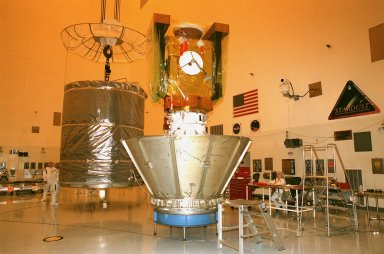 In the Payload Hazardous Servicing Facility, a canister (left) is moved toward the Stardust spacecraft (right). The protective canister will enclose Stardust before the spacecraft is moved to Launch Pad 17-A, Cape Canaveral Air Station, for launch preparations. Stardust is targeted for liftoff on Feb. 6 aboard a Boeing Delta II rocket for a close encounter with the comet Wild 2 in January 2004. Using a silicon-based substance called aerogel, Stardust will capture comet particles flying off the nucleus of the comet. The spacecraft also will bring back samples of interstellar dust. These materials consist of ancient pre-solar interstellar grains and other remnants left over from the formation of the solar system. Scientists expect their analysis to provide important insights into the evolution of the sun and planets and possibly into the origin of life itself. The collected samples will return to Earth in a sample return capsule to be jettisoned as Stardust swings by Earth in January 2006
