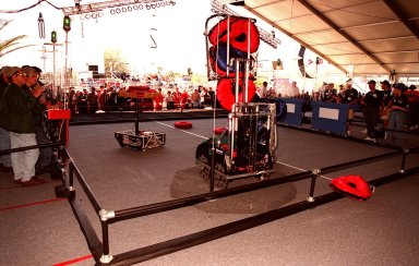 Student teams (right and left) behind protective walls maneuver their robots on the playing field during practice rounds of the 1999 Southeastern Regional robotic competition at Kennedy Space Center Visitor Complex . Thirty schools from around the country have converged at KSC for the event that pits gladiator robots against each other in an athletic-style competition. The robots have to retrieve pillow-like disks from the floor, as well as climb onto the platform (foreground) and raise the cache of pillows to a height of eight feet. KSC is hosting the event being sponsored by the nonprofit organization For Inspiration and Recognition of Science and Technology, known as FIRST. The FIRST robotics competition is designed to provide students with a hands-on, inside look at engineering and other professional careers