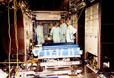 """In the Space Station Processing Facility, Marsha Ivins, a mission specialist on the STS-98 crew, inspects the U.S. Laboratory with members of the laboratory's processing team. The laboratory module, considered the centerpiece of the International Space Station (ISS), has been named """"Destiny"""" in honor of its prominent role in the world?s largest science and technology effort. It is planned for launch aboard Space Shuttle Endeavour on the sixth ISS construction flight currently targeted for March 2000. From left to right are Ivins, Danny Whittington (face not visible), Melissa Orozco, Jerry Hopkins, and Suzanne Fase"""
