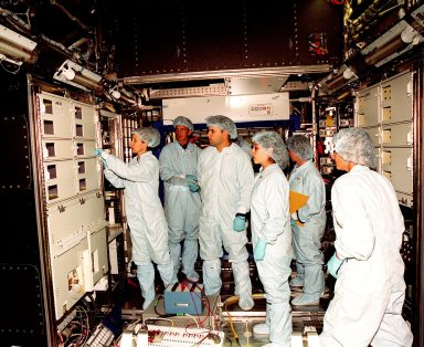 """In the Space Station Processing Facility, Marsha Ivins, a mission specialist on the STS-98 crew, inspects the U.S. Laboratory with members of the laboratory's processing team. The laboratory module, considered the centerpiece of the International Space Station (ISS), has been named """"Destiny"""" in honor of its prominent role in the world?s largest science and technology effort. It is planned for launch aboard Space Shuttle Endeavour on the sixth ISS construction flight currently targeted for March 2000. From left to right are Ivins, Jerry Hopkins, Danny Whittington, Melissa Orozco, Vicki Reese and Suzanne Fase"""