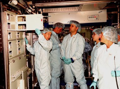 """In the Space Station Processing Facility, Marsha Ivins, a mission specialist on the STS-98 crew, inspects the U.S. Laboratory with members of the laboratory's processing team. The laboratory module, considered the centerpiece of the International Space Station (ISS), has been named """"Destiny"""" in honor of its prominent role in the world?s largest science and technology effort. It is planned for launch aboard Space Shuttle Endeavour on the sixth ISS construction flight currently targeted for March 2000. From left to right are Ivins, Jerry Hopkins, Danny Whittington, Melissa Orozco, and Suzanne Fase"""
