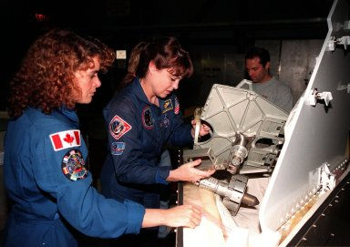 In the Orbiter Processing Facility bay 1, STS-96 Mission Specialists (left) Julie Payette, with the Canadian Space Agency, and Tamara Jernigan, Ph.D., look over the foot restraint used during space walks. The STS-96 crew is at KSC to take part in a Crew Equipment Interface Test. The other crew members are Commander Kent V. Rominger, Pilot Rick Douglas Husband, and Mission Specialists Ellen Ochoa (Ph.D), Daniel Barry (M.D., Ph.D.), and Valery Ivanovich Tokarev, who represents the Russian Space Agency. The primary payload of STS-96 is the SPACEHAB Double Module. In addition, the Space Shuttle will carry unpressurized cargo such as the external Russian cargo crane known as STRELA; the Spacehab Oceaneering Space System Box (SHOSS), which is a logistics items carrier; and an ORU Transfer Device (OTD), a U.S.-built crane that will be stowed on the station for use during future ISS assembly missions. These cargo items will be stowed on the International Cargo Carrier, fitted inside the payload bay behind the SPACEHAB module. STS-96 is targeted for launch on May 24 from Launch Pad 39B