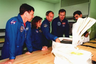 """KENNEDY SPACE CENTER, FLA. -- At the SPACEHAB Facility, members of the STS-101 crew look over equipment during familiarization activities. From left are Pilot Scott J. """"Doc"""" Horowitz (Ph.D.), Mission Specialists Mary Ellen Weber (Ph.D.) and Jeffrey N. Williams, and Commander James Donald Halsell Jr., plus Sean Hicks, with Boeing in Huntsville, Ala. Other crew members are Mission Specialists Edward Tsang Lu (Ph.D.), and Yuri Ivanovich Malenchenko and Boris Morukov, who represent the Russian Space Agency. Mission STS-101 is the third flight in construction of the International Space Station. The 11-day mission is targeted for launch on December 2, 1999, at Launch Pad 39A"""