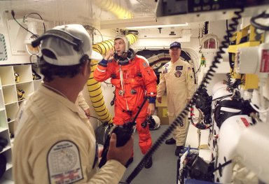 STS-96 Pilot Rick D. Husband is checked out by white room closeout crew members before entering the orbiter Discovery. At left is Closeout Chief Travis Thompson; at right is Quality Assurance Specialist James Davis. The white room is an environmental chamber at the end of the orbiter access arm that provides entry to the orbiter crew compartment. STS-96 is a 10-day logistics and resupply mission for the International Space Station, carrying about 4,000 pounds of supplies, to be stored aboard the station for use by future crews, including laptop computers, cameras, tools, spare parts, and clothing. The mission also includes such payloads as a Russian crane, the Strela; a U.S.-built crane; the Spacehab Oceaneering Space System Box (SHOSS), a logistics items carrier; and STARSHINE, a student-involved experiment. It will include a space walk to attach the cranes to the outside of the ISS for use in future construction. Space Shuttle Discovery is due to launch today at 6:49 a.m. EDT. Landing is expected at the SLF on June 6 about 1:58 a.m. EDT