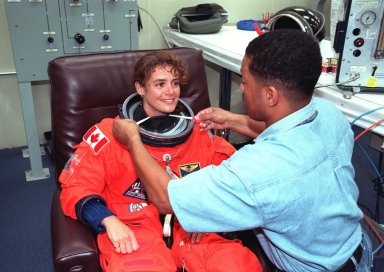 In the Operations and Checkout Building, STS-96 Mission Specialist Julie Payette is assisted by a suit technician in donning her launch and entry suit during final launch preparations. Payette is with the Canadian Space Agency. STS-96 is a 10-day logistics and resupply mission for the International Space Station, carrying about 4,000 pounds of supplies, to be stored aboard the station for use by future crews, including laptop computers, cameras, tools, spare parts, and clothing. The mission also includes such payloads as a Russian crane, the Strela; a U.S.-built crane; the Spacehab Oceaneering Space System Box (SHOSS), a logistics items carrier; and STARSHINE, a student-involved experiment. It will include a space walk to attach the cranes to the outside of the ISS for use in future construction.. Space Shuttle Discovery is due to launch today at 6:49 a.m. EDT. Landing is expected at the SLF on June 6 about 1:58 a.m. EDT