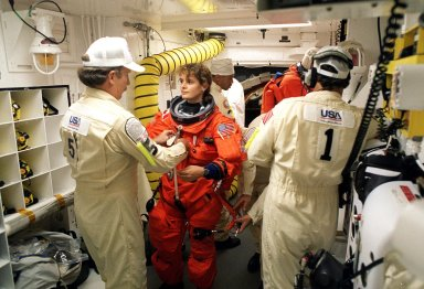 Before entering the orbiter Discovery, STS-96 Mission Specialist Julie Payette, with the Canadian Space Agency, is checked out in the white room by Quality Assurance Specialist James Davis (left) and Closeout Crew Chief Travis Thompson (right). In the background, Suit Technician Carlouse Gillis checks another crew member. The white room is an environmental chamber at the end of the orbiter access arm that provides entry to the orbiter crew compartment. STS-96 is a 10-day logistics and resupply mission for the International Space Station, carrying about 4,000 pounds of supplies, to be stored aboard the station for use by future crews, including laptop computers, cameras, tools, spare parts, and clothing. The mission also includes such payloads as a Russian crane, the Strela; a U.S.-built crane; the Spacehab Oceaneering Space System Box (SHOSS), a logistics items carrier; and STARSHINE, a student-involved experiment. It will include a space walk to attach the cranes to the outside of the ISS for use in future construction. Space Shuttle Discovery is due to launch today at 6:49 a.m. EDT. Landing is expected at the SLF on June 6 about 1:58 a.m. EDT