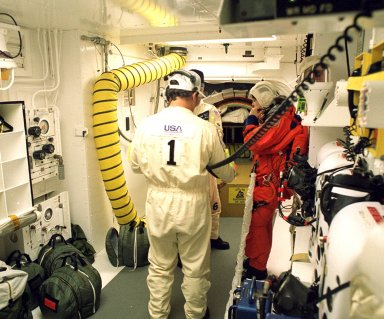 Before entering the orbiter Discovery, STS-96 Mission Specialist Tamara E. Jernigan is checked out in the white room by Closeout Crew Chief Travis Thompson (back to camera) and Quality Assurance Specialist James Davis. The white room is an environmental chamber at the end of the orbiter access arm that provides entry to the orbiter crew compartment. STS-96 is a 10-day logistics and resupply mission for the International Space Station, carrying about 4,000 pounds of supplies, to be stored aboard the station for use by future crews, including laptop computers, cameras, tools, spare parts, and clothing. The mission also includes such payloads as a Russian crane, the Strela; a U.S.-built crane; the Spacehab Oceaneering Space System Box (SHOSS), a logistics items carrier; and STARSHINE, a student-involved experiment. It will include a space walk to attach the cranes to the outside of the ISS for use in future construction. Space Shuttle Discovery is due to launch today at 6:49 a.m. EDT. Landing is expected at the SLF on June 6 about 1:58 a.m. EDT