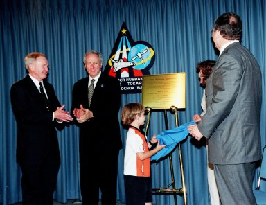 From left, Center Director Roy Bridges and NASA Administrator Daniel S. Goldin applaud as Jay Holliman, with the help of his mother, Mrs. Dianne Holliman, unveils a plaque honoring his father, the late John Holliman. At right is Tom Johnson, news group chairman of CNN. The occasion was the dedication of the KSC Press Site auditorium as the John Holliman Auditorium to honor the CNN national correspondent for his enthusiastic, dedicated coverage of America's space program. The auditorium was built in 1980 and has been the focal point for new coverage of Space Shuttle launches. The ceremony followed the 94th launch of a Space Shuttle, on mission STS-96, earlier this morning