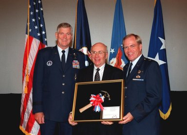 Commander of the Air Force Space Command, General Richard B. Myers (left) joins Ed Gormel (center) and Commander of the 45th Space Wing Brig. Gen. F. Randall Starbuck (right) after the presentation of the Hammer Award. The Hammer Award is Vice President Al Gore's special recognition of teams of federal employees who have made significant contributions in support of the principles of the National Partnership for Reinventing Government. Morley Winograd, director of the National Partnership for Reinventing Government, presented the award to the Joint Base Operations and Support Contract (J-BOSC) Source Evaluation Board (SEB). Gormel is a co-chair of the SEB. This Hammer Award acknowledges the accomplishments of a joint NASA and Air Force team that established the J-BOSC SEB. The team developed and implemented the acquisition strategy for establishing a single set of base operations and support service requirements for KSC, Cape Canaveral Air Station and Patrick Air Force Base
