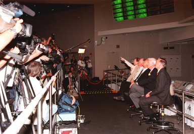 """KENNEDY SPACE CENTER, FLA. -- In the Apollo/Saturn V Center, Lisa Malone, chief of KSC's Media Services branch, identifies a reporter in the stands to pose a question to one of the former Apollo astronauts seated next to her. From left to right, they are Neil A. Armstrong and Edwin """"Buzz"""" Aldrin who flew on Apollo 11, the launch to the moon; Gene Cernan, who flew on Apollo 10 and 17; and Walt Cunningham, who flew on Apollo 7. Behind them on the lower floor are the original computer consoles used in the firing room during the Apollo program. They are now part of the reenactment of the Apollo launches in the exhibit at the center. This is the 30th anniversary of the launch and moon landing, July 16 and July 20, 1969. Neil Armstrong was the first man to set foot on the moon"""