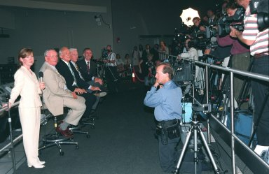 """KENNEDY SPACE CENTER, FLA. -- Photographers and cameramen fill the stands of the Apollo/Saturn V Center for a press conference with former Apollo astronauts (seated, left to right) Neil A. Armstrong and Edwin """"Buzz"""" Aldrin who flew on Apollo 11, the launch to the moon; Gene Cernan, who flew on Apollo 10 and 17; and Walt Cunningham, who flew on Apollo 7. At left is Lisa Malone, chief of KSC's Media Services branch, who monitored the session. The four astronauts were at KSC for the 30th anniversary of the Apollo 11 launch and moon landing, July 16 and July 20, 1969. Neil Armstrong was the first man to set foot on the moon"""