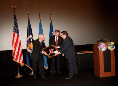 Ed Gormel (left) and Chris Fairey (center) accept the Hammer Award at a special presentation in the IMAX 2 Theater in the Kennedy Space Center Visitor Complex. Presenting the award is Morley Winograd (right), director of the National Partnership for Reinventing Government. The Hammer Award is Vice President Al Gore's special recognition of teams of federal employees who have made significant contributions in support of the principles of the National Partnership for Reinventing Government. This Hammer Award acknowledges the accomplishments of a joint NASA and Air Force team that established the Joint Base Operations and Support Contract (J-BOSC) Source Evaluation Board (SEB). Gormel and Fairey are co-chairs of the SEB. The team developed and implemented the acquisition strategy for establishing a single set of base operations and support service requirements for KSC, Cape Canaveral Air Station and Patrick Air Force Base