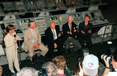 """KENNEDY SPACE CENTER, FLA. -- In this closeup viewed from above, former Apollo astronauts (seated, left to right) Neil A. Armstrong and Edwin """"Buzz"""" Aldrin who flew on Apollo 11, the launch to the moon; Gene Cernan, who flew on Apollo 10 and 17; and Walt Cunningham, who flew on Apollo 7, answer questions from the media during a press conference in the Apollo/Saturn V Center. At left is Lisa Malone, chief of KSC's Media Services branch, who monitored the session. In the background are the original computer consoles used in the firing room during the Apollo program. They are now part of the reenactment of the Apollo launches in the exhibit at the center. The four astronauts were at KSC for the 30th anniversary of the Apollo 11 launch and moon landing, July 16 and July 20, 1969"""