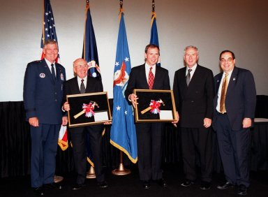 At a special presentation in the IMAX 2 Theater in the Kennedy Space Center Visitor Complex, the Hammer Award is presented to Kennedy Space Center and the 45th Space Wing. Present for the awards are (left to right) Commander of the Air Force Space Command General Richard B. Myers, Ed Gormel, Chris Fairey, NASA Administrator Daniel Goldin, and Director of the National Partnership for Reinventing Government, Morley Winograd, who presented the award. The Hammer Award is Vice President Al Gore's special recognition of teams of federal employees who have made significant contributions in support of the principles of the National Partnership for Reinventing Government. This Hammer Award acknowledges the accomplishments of a joint NASA and Air Force team that established the Joint Base Operations and Support Contract (J-BOSC) Source Evaluation Board (SEB). Gormel and Fairey are co-chairs of the SEB. The team developed and implemented the acquisition strategy for establishing a single set of base operations and support service requirements for KSC, Cape Canaveral Air Station and Patrick Air Force Base