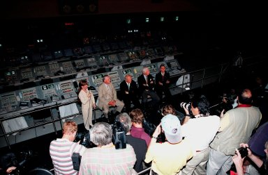 """KENNEDY SPACE CENTER, FLA. -- Viewed from above, former Apollo astronauts (seated, left to right) Neil A. Armstrong and Edwin """"Buzz"""" Aldrin who flew on Apollo 11, the launch to the moon; Gene Cernan, who flew on Apollo 10 and 17; and Walt Cunningham, who flew on Apollo 7, answer questions from the media during a press conference in the Apollo/Saturn V Center. At left is Lisa Malone, chief of KSC's Media Services branch, who monitored the session. In the background are the original computer consoles used in the firing room during the Apollo program. They are now part of the reenactment of the Apollo launches in the exhibit at the center. The four astronauts were at KSC for the 30th anniversary of the Apollo 11 launch and moon landing, July 16 and July 20, 1969"""