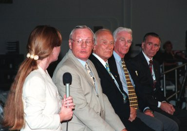 """KENNEDY SPACE CENTER, FLA. -- In the Apollo/Saturn V Center, Lisa Malone (left), chief of KSC's Media Services branch, relays a question from the media to former Apollo astronaut Neil A. Armstrong. Beside Armstrong are Edwin """"Buzz"""" Aldrin, Gene Cernan, and Walt Cunningham, all of whom also flew on Apollo missions. The four met with the media prior to an anniversary banquet highlighting the contributions of aerospace employees who made the Apollo program possible. The banquet celebrated the 30th anniversary of the launch and moon landing, July 16 and July 20, 1969. Neil Armstrong was the first man to set foot on the moon"""