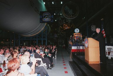 """KENNEDY SPACE CENTER, FLA. -- NASA Administrator Daniel S. Goldin (right) addresses the audience at the Apollo 11 anniversary banquet honoring the Apollo team, the people who made the entire lunar landing program possible. The banquet was held in the Apollo/Saturn V Center, part of the KSC Visitor Complex, with seating under an unused Saturn V rocket like those that powered the Apollo launches . This is the 30th anniversary of the Apollo 11 launch and moon landing, July 16 and July 20, 1969. Among the guests at the banquet were former Apollo astronauts are Neil A. Armstrong and Edwin """"Buzz"""" Aldrin who flew on Apollo 11, the launch of the first moon landing; Gene Cernan, who flew on Apollo 10 and 17 and was the last man to walk on the moon; and Walt Cunningham, who flew on Apollo 7"""