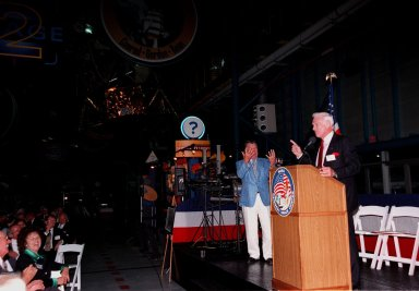 """KENNEDY SPACE CENTER, FLA. -- During an anniversary banquet honoring the Apollo program team, the people who made the entire lunar landing program possible, former Apollo astronaut Gene Cernan relates a humorous comment while Wally Schirra (background) gestures behind him. Cernan, who flew on Apollo 10 and 17, was the last man to walk on the moon; Schirra flew on Apollo 7. The banquet was held in the Apollo/Saturn V Center, part of the KSC Visitor Complex. This is the 30th anniversary of the Apollo 11 launch and moon landing, July 16 and July 20, 1969. Other guests at the banquet were former Apollo astronauts are Neil A. Armstrong and Edwin """"Buzz"""" Aldrin who flew on Apollo 11, the launch of the first moon landing, and Walt Cunningham, who also flew on Apollo 7"""