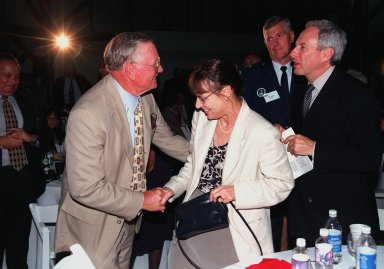 """KENNEDY SPACE CENTER, FLA. -- During an anniversary banquet honoring the Apollo team, the people who made the entire lunar landing program possible, former Apollo astronaut Neil A. Armstrong (left) shakes the hand of Judy Goldin (center), wife of NASA Administrator Daniel S. Goldin (right). The banquet was held in the Apollo/Saturn V Center, part of the KSC Visitor Complex. This is the 30th anniversary of the Apollo 11 launch and moon landing, July 16 and July 20, 1969. Among the guests at the banquet were former Apollo astronauts are Neil A. Armstrong and Edwin """"Buzz"""" Aldrin who flew on Apollo 11, the launch of the first moon landing; Gene Cernan, who flew on Apollo 10 and 17 and was the last man to walk on the moon; and Walt Cunningham, who flew on Apollo 7"""