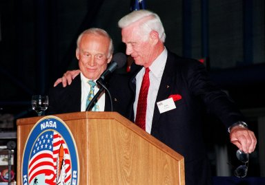 """KENNEDY SPACE CENTER, FLA. -- Former Apollo astronauts Edwin """"Buzz"""" Aldrin (left) and Gene Cernan share stories about their missions for an audience attending an anniversary banquet honoring the Apollo program team, the people who made the entire lunar landing program possible. The banquet was held in the Apollo/Saturn V Center, part of the KSC Visitor Complex. This is the 30th anniversary of the Apollo 11 launch and moon landing, July 16 and July 20, 1969. Other guests at the banquet were astronauts Wally Schirra, Gene Cernan and Walt Cunningham. Neil Armstrong was the first man to walk on the moon; Gene Cernan was the last"""
