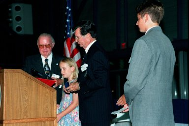 """KENNEDY SPACE CENTER, FLA. -- George Meguiar (left) presents a scholarship award to Kyla Davis Horn, of Cocoa Beach, one of the winners of an essay contest related to the 30th Anniversary of Apollo 11. Meguiar and George English (second from right) head the Apollo 11 Commemoration Association who sponsored the contest in conjunction with Florida Today newspaper. The other scholarship winner is Kyle Rukaczewski, of Satellite Beach (far right). A third winner, Jason Gagnon, of Viera, was unable to attend. The presentation was made at the Apollo/Saturn V Center during an anniversary banquet that honored all the people who made the Apollo Program possible. Special guests included former Apollo astronauts Neil Armstrong, Edwin """"Buzz"""" Aldrin, Gene Cernan and Walt Cunningham, who shared their experiences with the audience"""