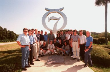 At Cape Canaveral Air Station, members of the 1998 astronaut candidate class (Group 17) pose in front of the Project Mercury monument at Launch Complex 14 during a tour of the station's facilities. This 13-foot-high astronomical symbol for the planet Mercury was constructed by General Dynamics, the Atlas airframe contractor, and dedicated in 1964 in honor of those who flew in the Mercury 7 capsule. The class is at Kennedy Space Center taking part in training activities, including a flight awareness program, as well as touring the OPF, VAB, SSPF, SSME Processing Facility, launch pads, SLF, Apollo/Saturn V Center, and the crew quarters. The U.S. candidates in the '98 class are Clayton C. Anderson, Lee J. Archambault, Tracy E. Caldwell (Ph.D.), Gregory E. Chamitoff (Ph.D.), Timothy J. Creamer, Christopher J. Ferguson, Michael J. Foreman, Michael E. Fossum, Kenneth T. Ham, Patricia C. Hilliard (M.D.), Gregory C. Johnson, Gregory H. Johnson, Stanley G. Love (Ph.D.), Leland D. Melvin, Barbara R. Morgan, William A. Oefelein, John D. Olivas (Ph.D.), Nicholas J.M. Patrick (Ph.D.), Alan G. Poindexter, Garrett E. Reisman (Ph.D.), Steven R. Swanson, Douglas H. Wheelock, Sunita L. Williams, Neil W. Woodward III, George D. Zamka; and the international candidates are Leopold Eyharts, Paolo Nespoli, Hans Schlegel, Roberto Vittori, Bjarni V. Tryggvason, and Marcos Pontes