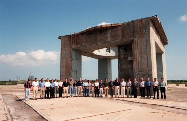 At Cape Canaveral Air Station, members of the 1998 astronaut candidate class (Group 17) pose in front of what remains of the launch tower at Launch Complex 34 during a tour of the station's facilities. During the Apollo Program, Launch Complex 34 was the site of the first Saturn I and Saturn IB launches, as well as the tragic fire in which the Apollo I astronauts lost their lives. The class is at Kennedy Space Center taking part in training activities, including a flight awareness program, as well as touring the OPF, VAB, SSPF, SSME Processing Facility, launch pads, SLF, Apollo/Saturn V Center, and the crew quarters. The U.S. candidates in the '98 class are Clayton C. Anderson, Lee J. Archambault, Tracy E. Caldwell (Ph.D.), Gregory E. Chamitoff (Ph.D.), Timothy J. Creamer, Christopher J. Ferguson, Michael J. Foreman, Michael E. Fossum, Kenneth T. Ham, Patricia C. Hilliard (M.D.), Gregory C. Johnson, Gregory H. Johnson, Stanley G. Love (Ph.D.), Leland D. Melvin, Barbara R. Morgan, William A. Oefelein, John D. Olivas (Ph.D.), Nicholas J.M. Patrick (Ph.D.), Alan G. Poindexter, Garrett E. Reisman (Ph.D.), Steven R. Swanson, Douglas H. Wheelock, Sunita L. Williams, Neil W. Woodward III, George D. Zamka; and the international candidates are Leopold Eyharts, Paolo Nespoli, Hans Schlegel, Roberto Vittori, Bjarni V. Tryggvason, and Marcos Pontes
