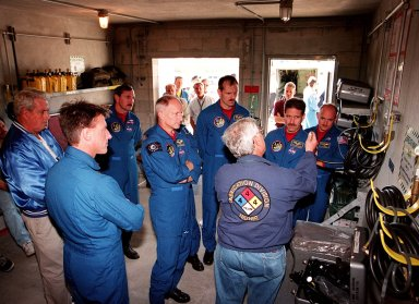 "Inside a bunker at Launch Pad 39B, the STS-103 crew are instructed about use of the equipment. From left (in their astronaut uniforms) are Mission Specialist C. Michael Foale (Ph.D.), Commander Curtis L. Brown Jr., Mission Specialists Claude Nicollier of Switzerland, Steven L. Smith, John M. Grunsfeld (Ph.D.), and Pilot Steven J. Kelly. Not shown in the photo is Mission Specialist Jean-François Clervoy of France. Nicollier and Clervoy are both with the European Space Agency. As a preparation for launch, the crew have been participating in Terminal Countdown Demonstration Test (TCDT) activities at KSC. The TCDT provides the crew with emergency egress training, opportunities to inspect their mission payloads in the orbiter's payload bay, and simulated countdown exercises. STS-103 is a ""call-up"" mission due to the need to replace and repair portions of the Hubble Space Telescope, including the gyroscopes that allow the telescope to point at stars, galaxies and planets. The STS-103 crew will be replacing a Fine Guidance Sensor, an older computer with a new enhanced model, an older data tape recorder with a solid-state digital recorder, a failed spare transmitter with a new one, and degraded insulation on the telescope with new thermal insulation. The crew will also install a Battery Voltage/Temperature Improvement Kit to protect the spacecraft batteries from overcharging and overheating when the telescope goes into a safe mode. Four EVA's are planned to make the necessary repairs and replacements on the telescope. The mission is targeted for launch Dec. 6 at 2:37 a.m. EST"