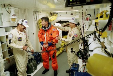KENNEDY SPACE CENTER, FLA. -- STS-103 Mission Specialist C. Michael Foale (Ph.D.), in his orange launch and entry suit, is assisted by closeout crew members in the White Room before entering the orbiter. At left is United Space Alliance (USA) Orbiter Vehicle Closeout Chief Travis Thompson and USA Mechanical Technician Vinny Defranzo. The White Room is an environmental chamber at the end of the orbiter access arm on the fixed service structure. It provides entry to the orbiter crew compartment. The mission, to service the Hubble Space Telescope, is scheduled to lift off at 7:50 p.m. EST Dec. 19 on mission STS-103, servicing the Hubble Space Telescope. Objectives for the nearly eight-day mission include replacing gyroscopes and an old computer, installing another solid state recorder, and replacing damaged insulation in the telescope. Discovery is expected to land at KSC Monday, Dec. 27, at about 5:24 p.m. EST
