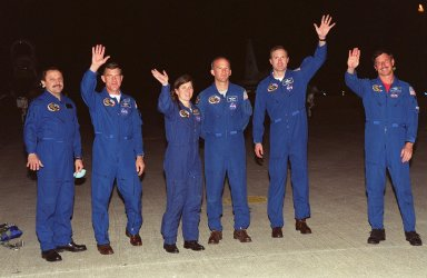 KENNEDY SPACE CENTER, FLA. -- Members of the STS-101 crew wave at media and photographers at KSC's Shuttle Landing Facility after their landing the night of May 14. Standing left to right are Mission Specialists Yuri Usachev, James Voss, Mary Ellen Weber and Jeff Williams; Commander James Halsell; and Pilot Scott Horowitz. Not present is Mission Specialist Susan Helms, who arrived later. The crew will be preparing for the launch on May 18. The mission will take the crew of seven to the International Space Station, delivering logistics and supplies, plus preparing the Station for the arrival of the Zvezda Service Module, expected to be launched by Russia in July 2000. Also, the crew will conduct one space walk to perform maintenance on the Space Station. This will be the third assembly flight for the Space Station. STS-101 is targeted for liftoff at 6:38 a.m. EDT from Launch Pad 39A