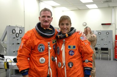 KENNEDY SPACE CENTER, FLA. - In the Operations and Checkout Building at NASA Kennedy Space Center, STS-115 Mission Specialists Joseph Tanner and Heidemarie Stefanyshyn-Piper pose while suiting up for the ride to Launch Pad 39B and another attempt at liftoff. The launch attempt on Sept. 8 was scrubbed due to an issue with a fuel cut-off sensor system inside the external fuel tank. This is one of several systems that protect the shuttle's main engines by triggering their shutdown if fuel runs unexpectedly low. During the STS-115 mission, Atlantis' astronauts will deliver and install the 17.5-ton, bus-sized P3/P4 integrated truss segment on the station. The girder-like truss includes a set of giant solar arrays, batteries and associated electronics and will provide one-fourth of the total power-generation capability for the completed station. This mission is the 116th space shuttle flight, the 27th flight for orbiter Atlantis, and the 19th U.S. flight to the ISS. STS-115 is scheduled to last 11 days with a planned landing at KSC. Photo credit: NASA/Kim Shiflett