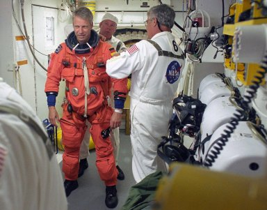 KENNEDY SPACE CENTER, FLA. - In the White Room on Launch Pad 39B, STS-121 Mission Specialist Thomas Reiter is helped by the Closeout Crew to prepare for entering Discovery and the launch. Situated on the end of the orbiter access arm, the White Room provides access into the orbiter on the pad. The crew is preparing for the third launch attempt in four days; previous attempts were scrubbed due to weather concerns. During the 12-day mission, the STS-121 crew will test new equipment and procedures to improve shuttle safety, as well as deliver supplies and make repairs to the International Space Station. The launch of Space Shuttle Discovery on mission STS-121 is the 115th shuttle flight and the 18th U.S. flight to the International Space Station. Photo credit: NASA/Regina Mitchell-Ryall & Tony Gray
