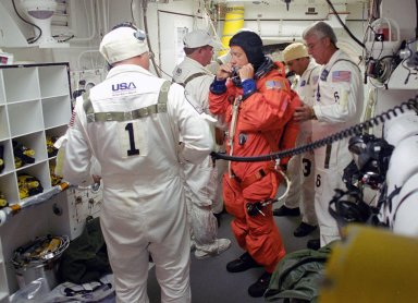 KENNEDY SPACE CENTER, FLA. - In the White Room on Launch Pad 39B, STS-121 Commander Steven Lindsey is helped by the Closeout Crew to prepare his launch suit for entering Discovery and the launch. Situated on the end of the orbiter access arm, the White Room provides access into the orbiter on the pad. The crew is preparing for the third launch attempt in four days; previous attempts were scrubbed due to weather concerns. During the 12-day mission, the STS-121 crew will test new equipment and procedures to improve shuttle safety, as well as deliver supplies and make repairs to the International Space Station. The launch of Space Shuttle Discovery on mission STS-121 is the 115th shuttle flight and the 18th U.S. flight to the International Space Station. Photo credit: NASA/Regina Mitchell-Ryall & Tony Gray