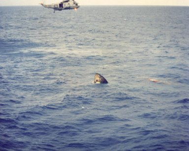 JOHNSON SPACE CENTER, HOUSTON, TEXAS - A recovery helicopter hovers above the Apollo 11 spacecraft seconds after it splashed down in the Pacific Ocean July 24, 1969, at 12:50 p.m. EDT 900 miles southwest of Hawaii. The spacecraft turned apex down after impact, as shown here, but inflatable bags repositioned it shortly after this view was taken.