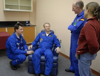 KENNEDY SPACE CENTER, FLA. -- European Space Agency astronaut Thomas Reiter (seated), returning from a 6-month stay on the International Space Station, talks to colleagues in the crew quarters at Kennedy Space Center. Reiter returned to Earth with the STS-116 crew aboard Space Shuttle Discovery. Landing took place on Runway 15 at NASA Kennedy Space Center's Shuttle Landing Facility as the sun set on the shortest day of the year. During the STS-116 mission, three spacewalks attached the P5 integrated truss structure to the station, and completed the rewiring of the orbiting laboratory's power system. A fourth spacewalk retracted a stubborn solar array. Main gear touchdown was at 5:32 p.m. EST. Nose gear touchdown was at 5:32:12 p.m. and wheel stop was at 5:32:52 p.m. At touchdown -- nominally about 2,500 ft. beyond the runway threshold -- the orbiter is traveling at a speed ranging from 213 to 226 mph. Discovery traveled 5,330,000 miles, landing on orbit 204. Mission elapsed time was 12 days, 20 hours, 44 minutes and 16 seconds. This is the 64th landing at KSC. Photo credit: NASA/Kim Shiflett