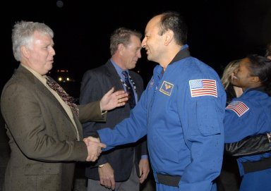 KENNEDY SPACE CENTER, FLA. -- Kennedy Space Center Director Jim Kennedy welcomes STS-116 Commander Mark Polansky back to Earth as United Space Alliance President and CEO Mike McCulley talks to Mission Specialist Joan Higginbotham in the background. The informal gathering followed the landing of Space Shuttle Discovery on Runway 15 at NASA Kennedy Space Center's Shuttle Landing Facility at 5:32 p.m. EST. During the STS-116 mission, three spacewalks attached the P5 integrated truss structure to the station, and completed the rewiring of the orbiting laboratory's power system. A fourth spacewalk retracted a stubborn solar array. Main gear touchdown was at 5:32 p.m. EST. Nose gear touchdown was at 5:32:12 p.m. and wheel stop was at 5:32:52 p.m. At touchdown -- nominally about 2,500 ft. beyond the runway threshold -- the orbiter is traveling at a speed ranging from 213 to 226 mph. Discovery traveled 5,330,000 miles, landing on orbit 204. Mission elapsed time was 12 days, 20 hours, 44 minutes and 16 seconds. This is the 64th landing at KSC. Photo credit: NASA/Kim Shiflett