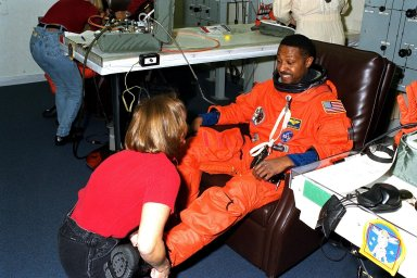 STS-87 Mission Specialist Winston Scott dons his launch and entry suit with the assistance of a suit technician in the Operations and Checkout Building. This is Scott?s second space flight. He and the five other crew members will depart shortly for Launch Pad 39B, where the Space Shuttle Columbia awaits liftoff on a 16-day mission to perform microgravity and solar research. Scott is scheduled to perform an extravehicular activity spacewalk with Mission Specialist Takao Doi, Ph.D., of the National Space Development Agency of Japan, during STS-87. He also performed a spacewalk on STS-72