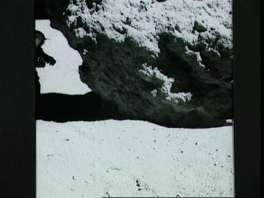 Astronaut John Young looks over a boulder at Station no. 13 during EVA