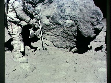 """Astronaut Charles Duke stands at rock adjacent to """"House Rock"""