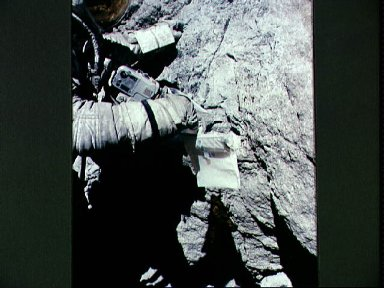 Astronaut Charles Duke examines surface of boulder at North Ray crater